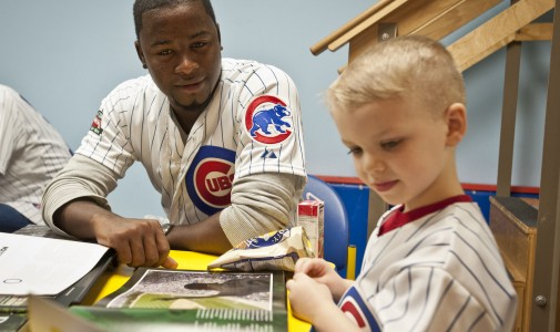 Cubs prospect Arodys Vizcaino looks through a Wrigley Field book with this little guy.